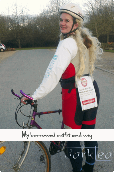 A person posing with a bike and wig in a parking lot