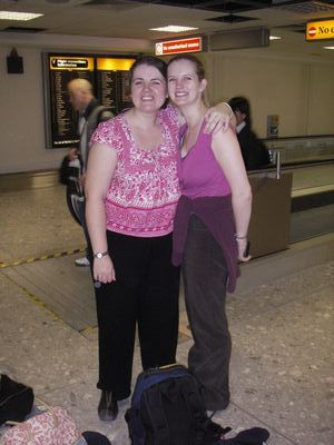 Two woman standing next to a bag of luggage at an airport
