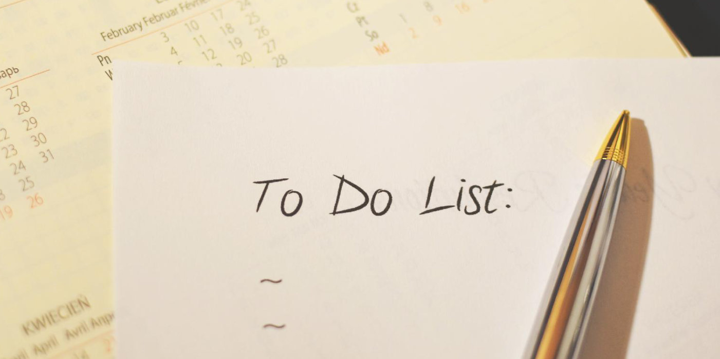 a calendar, pen and a piece of paper with handwriting that says To Do List
