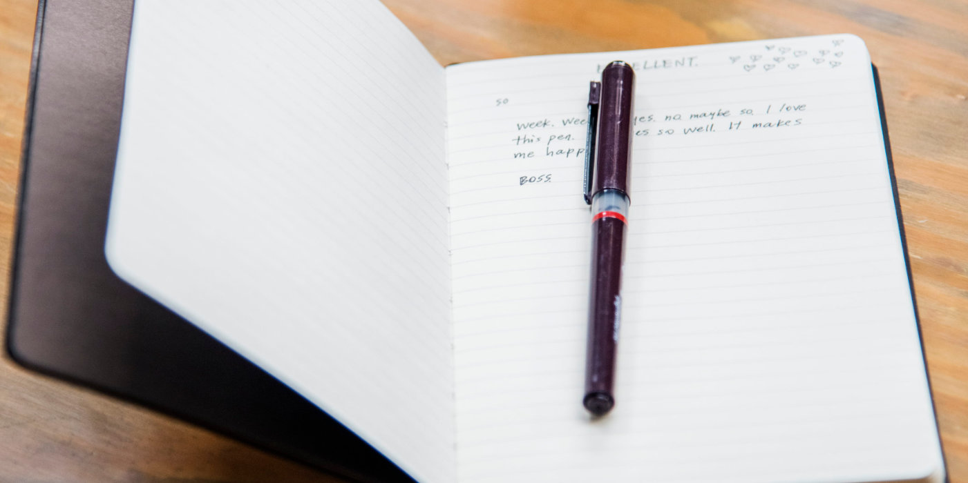 notebook open with a pen on its first page