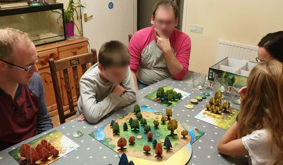 group of adults and children playing photosynthesis board game
